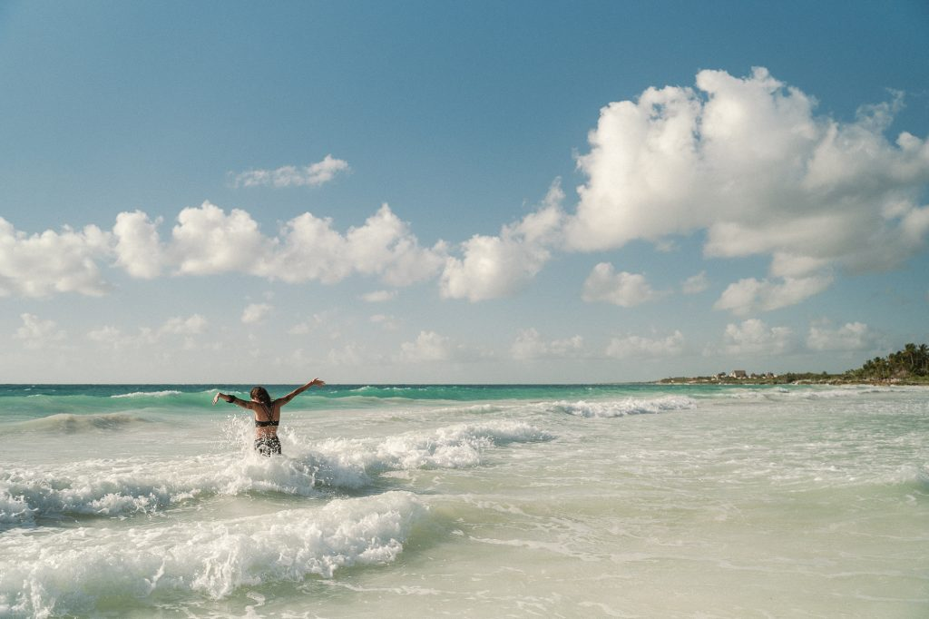 Girl playing in the waves at Tulum, Mexico