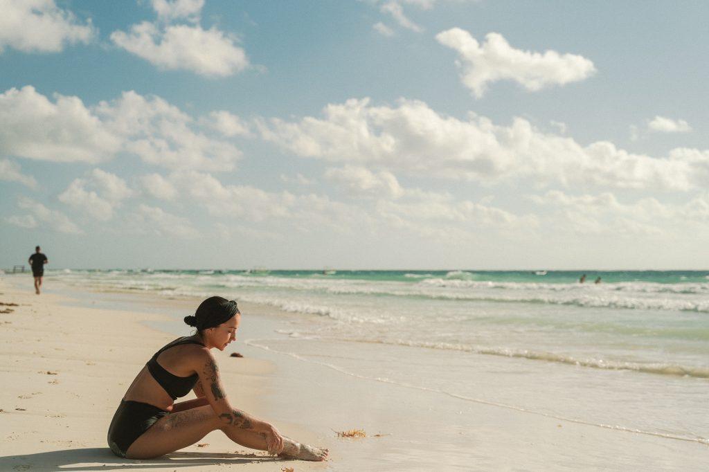Girl sat on beach at Tulum, Mexico