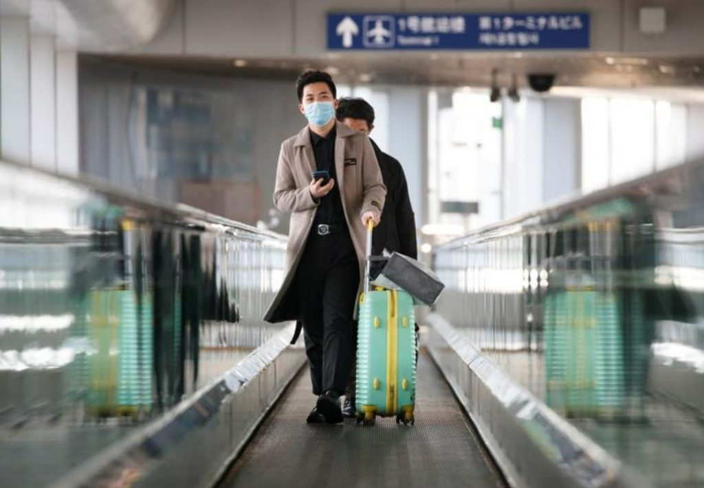 business traveler wearing a mask at an airport